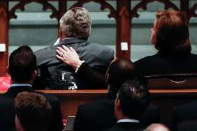 """Dorothy """"Doro"""" Bush Koch wraps her arm around her father, former president George H.W. Bush, during the funeral for former first lady Barbara Bush at St. Martin's Episcopal Church on Saturday, April 21, 2018, in Houston."""