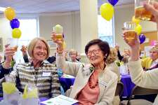 """The founder of At Home in Greenwich, Marilyn Chou, center, smiled as she was honored and toasted during the 10th anniversary celebration of the At Home in Greenwich organization at the Second Congregational Church in Greenwich, Conn., April 17, 2018. The stated mission of At Home in Greenwich, according to their website is, """"To enable Greenwich seniors to confidently age in place by providing stimulating social and educational programs and assistance with matters of health and safety."""""""