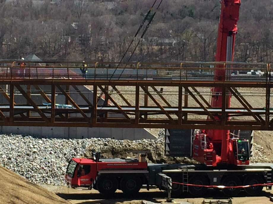 A 130-foot crane provided by A-Quick Pick in Derby lifts the 80,000 pound steel bridge walkway for the Ansonia Riverwalk on Pershing Drive. Photo: / Michael P. Mayko