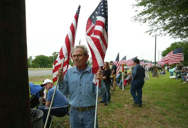 Bert McCormik carries two, out of the 65 American flags, he brought to watch the motorcade for former First Lady Barbara Bush pass by Frazier's Ornamental Concrete store, which is next to Highway 6 Saturday, April 21, 2018, in Hempstead, Texas. Photo: Godofredo A. Vasquez, Houston Chronicle / Godofredo A. Vasquez