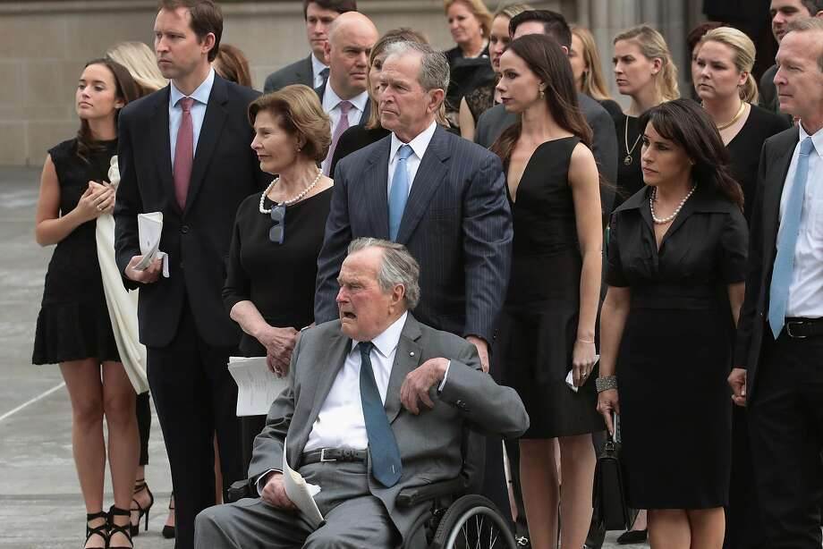 Former President George H.W. Bush and his oldest son, former President George W. Bush, watch with family as former first lady Barbara Bush's coffin is placed in a hearse in Houston. Photo: Scott Olson / Getty Images