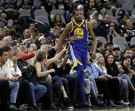 Fans help Golden State Warriors' Kevin Durant (35) from falling into the seating area in the second half of Game 3 of a first-round NBA basketball playoff series against the San Antonio Spurs in San Antonio, Thursday, April 19, 2018. Golden State won 110-97. (AP Photo/Eric Gay)