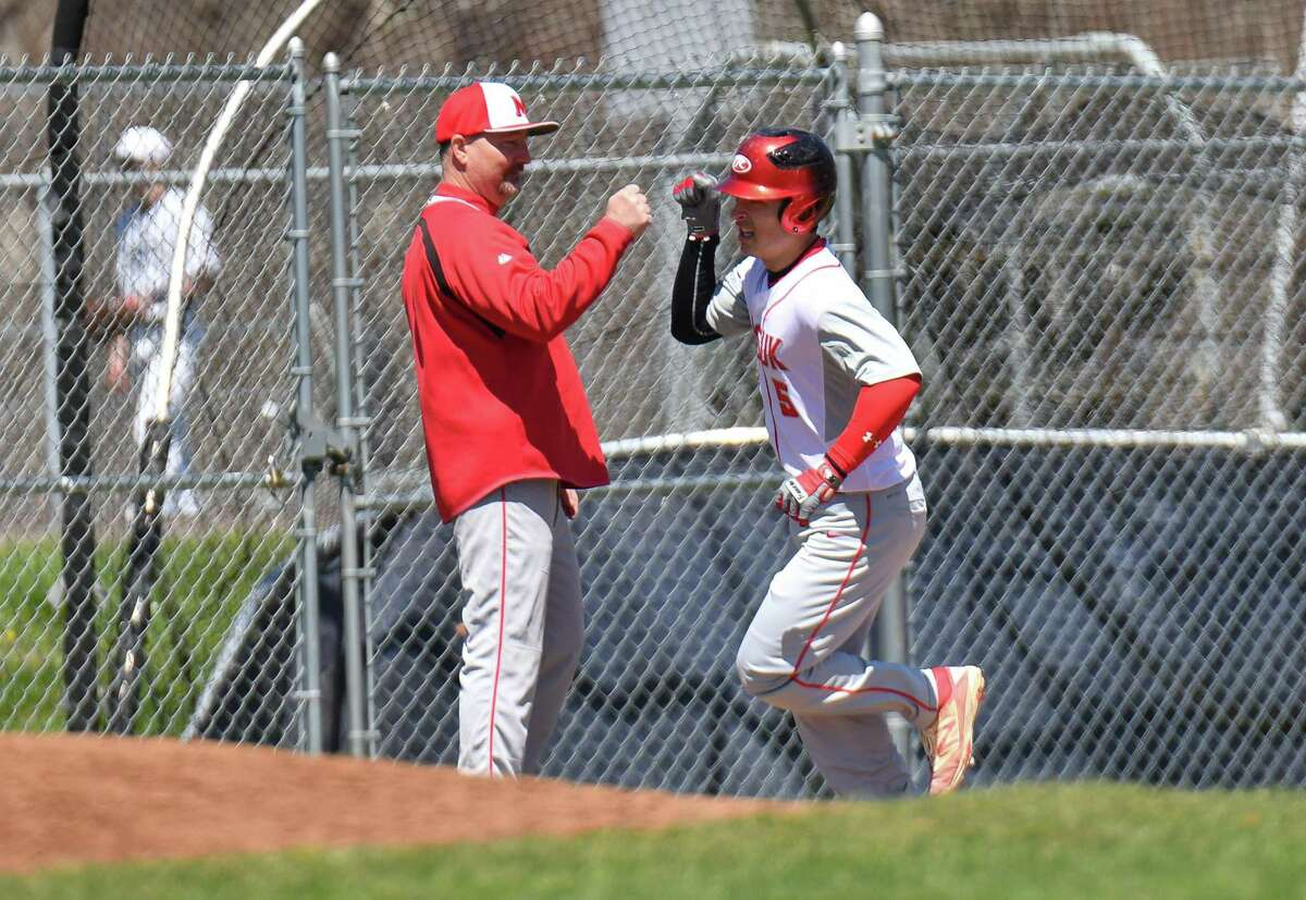 Enzo Merlonghi (5) of the Masuk Panthers gets a high five from coach Ralph Franco as he rounds third base after hitting a home run during a game against the Staples Wreckers at Staples High School on Saturday April 21, 2018 in Westport, Connecticut.