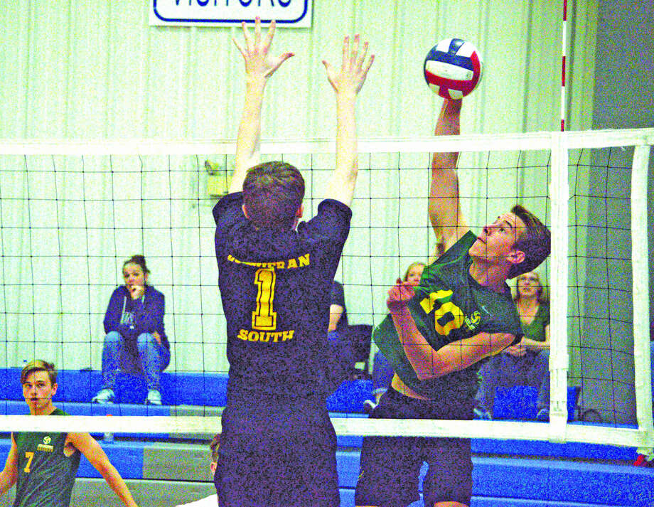 Metro-East Lutheran senior Caleb Cope, right, goes for a kill during Saturday's third-place match against Lutheran South in the Cougar Invitational at Lutheran St. Charles.