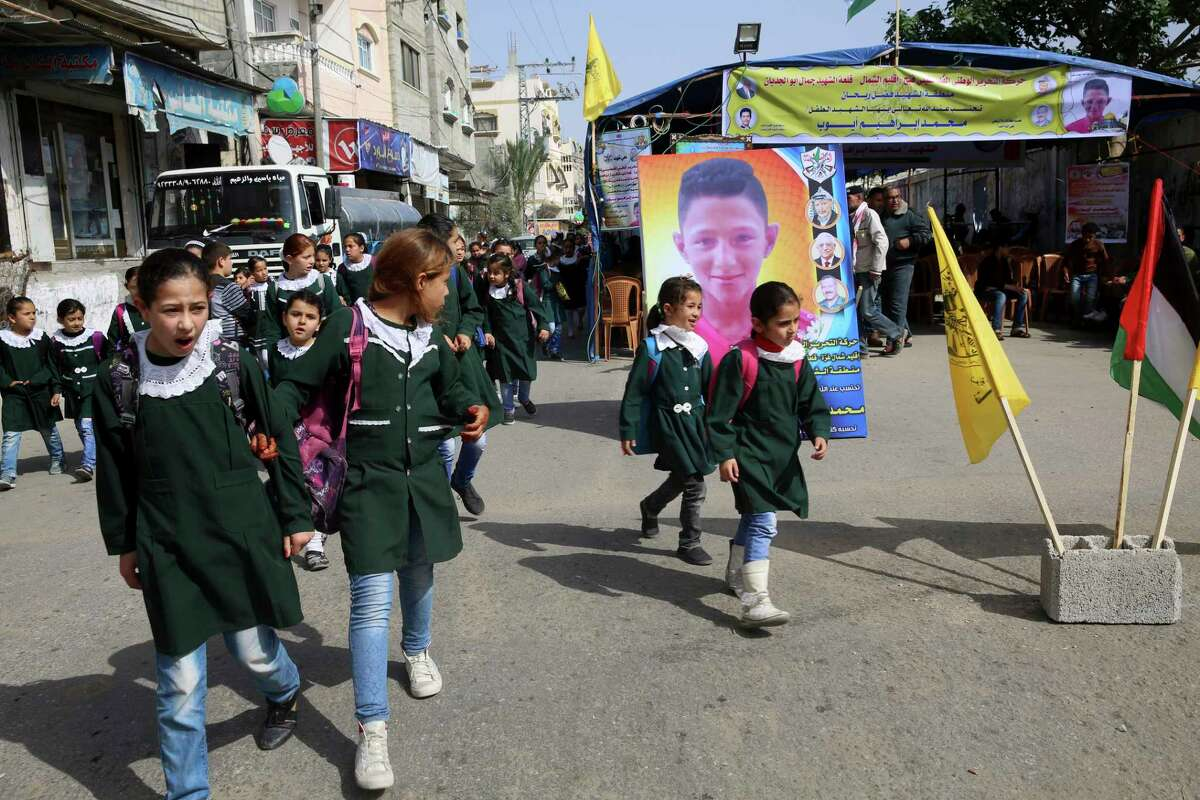 """School girls look while pass the house morning of Mohammed Ayyoub, 14, who was killed during a protest along Gaza's border with Israel, east of Jebaliya Yesterday, at the main road in Jebaliya refugee camp, Gaza Strip, Saturday, April 21, 2018. Israel's defense minister said Saturday that Hamas leaders are the """"only culprits"""" in continued bloodshed on the Gaza border, as the EU and a top U.N. official made new demands to investigate shootings of unarmed Palestinians by Israeli soldiers, including the killing of a 14-year-old boy. (AP Photo/Adel Hana)"""