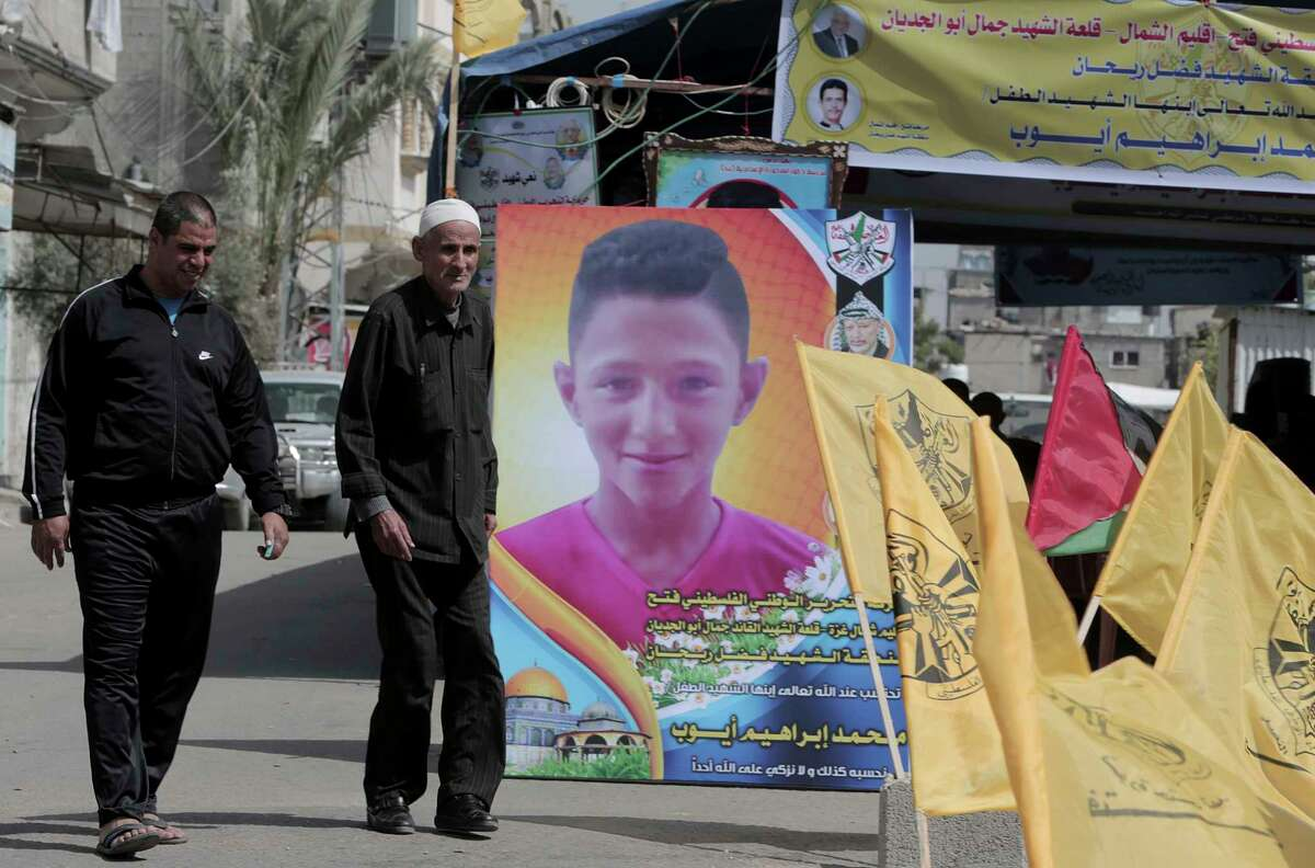 """Residents arrive to the house morning of Mohammed Ayyoub, 14, who was killed during a protest along Gaza's border with Israel, east of Jebaliya Yesterday, at the main road in Jebaliya refugee camp, Gaza Strip, Saturday, April 21, 2018. Israel's defense minister said Saturday that Hamas leaders are the """"only culprits"""" in continued bloodshed on the Gaza border, as the EU and a top U.N. official made new demands to investigate shootings of unarmed Palestinians by Israeli soldiers, including the killing of a 14-year-old boy. (AP Photo/Adel Hana)"""