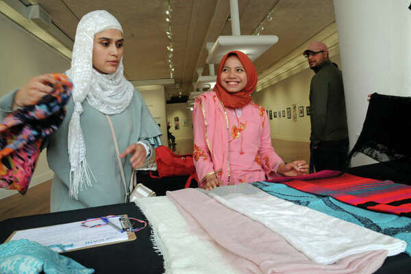 "Moji Sidiqi puts her hand-made clothing on display while Lydia Apraliani watches during ""Meet a Muslim"" at the Jacoby Arts Center, part of Alton Main Street's Small Town - Big World event."
