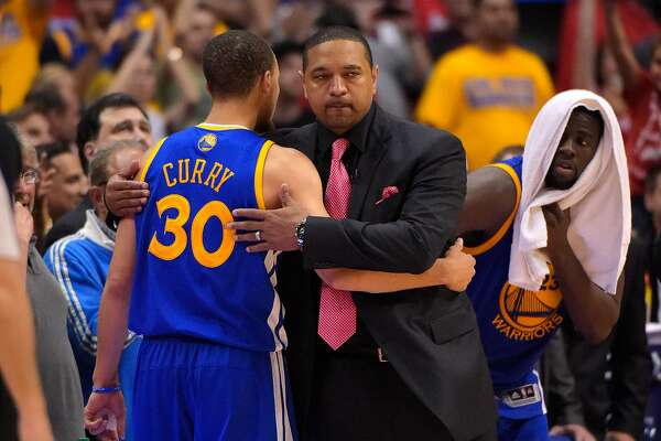 Golden State Warriors head coach Mark Jackson, center, hugs guard Stephen Curry after Curry was taken out of the game as forward Draymond Green looks on during the second half in Game 7 of an opening-round NBA basketball playoff series, Saturday, May 3, 2014, in Los Angeles. The Clippers won 126-121. (AP Photo/Mark J. Terrill)