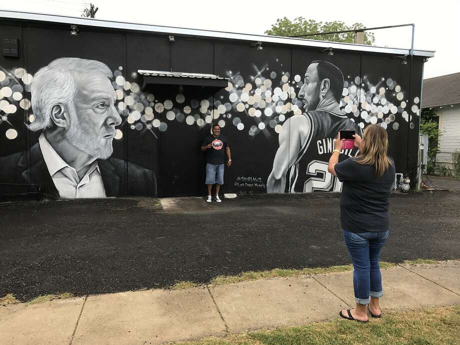 Leonard Rodriguez gets his photo taken by Patricia Garcia at the new Spurs mural on the side of Rudy's Seafood in San Antonio, where fans love Gregg Popovich and Manu Ginobili. Photo: Scott Ostler / The Chronicle