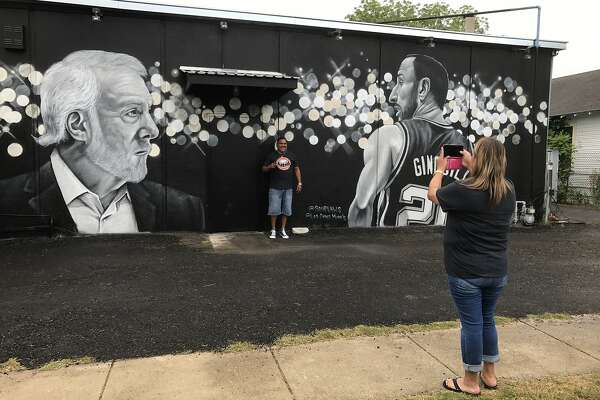 Leonard Rodriguez gets his photo taken by Patricia Garcia from San Antonio, Texas in front of Gregg Popovich mural on the side of Rudy's Seafood in San Antonio, Texas.