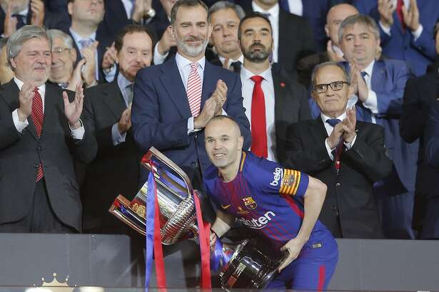 Barcelona's captain Andres Iniesta, centre, lifts the trophy which he received from Spain's King Felipe, during an award ceremony after defeating Sevilla 5-0 in the Copa del Rey final soccer match at the Wanda Metropolitano stadium in Madrid, Spain, Saturday, April 21, 2018. (AP Photo/Paul White)