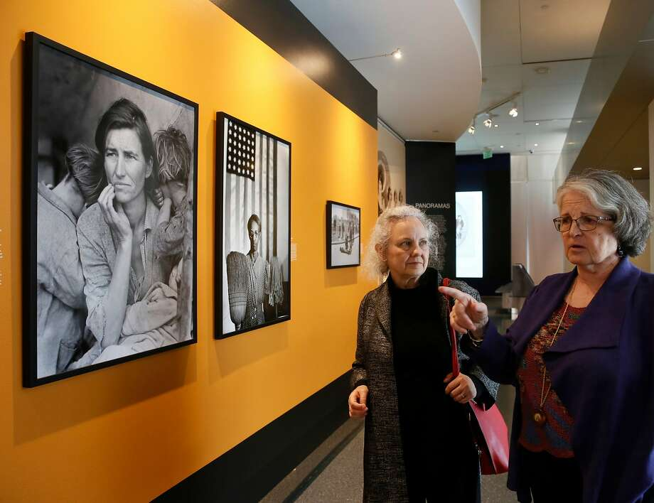 "Photo curator Beverly Brannan (left) and exhibition curator Anne Wilkes Tucker discuss Dorothea Lange's 1936 farmworker portrait ""Migrant Mother."" Photo: Damian Dovarganes / Associated Press"