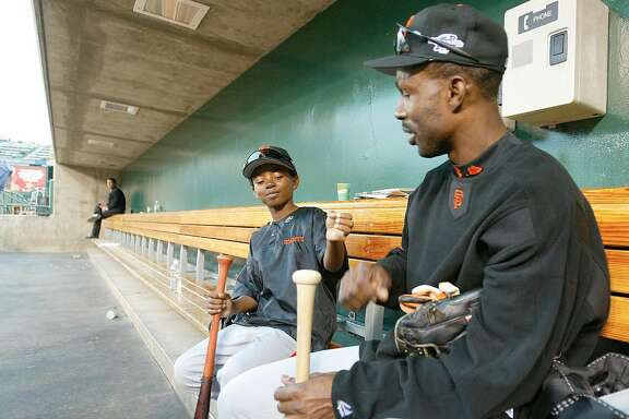 GIANTS23-C-18OCT02-SP-MAC            Giants Shawon Dunston along with his 9 year old son Shawon Jr. inside the dugout at the end of  San Francisco's final workout   before the start of the series tomorrow. San Francsico Giants during workouts one day before the start of the Wold Series.             by Michael Macor/The Chronicle
