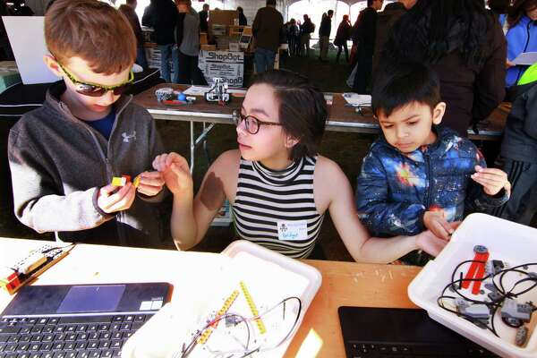 Briget Groves, with Compuchild of Westport, helps Jonah Black, 7, left, and Ishaan Ajmera, 5, with their computer operated Lego creations during the 7th Annual Maker Faire Westport in downtown Westport, Conn., on Saturday Apr. 21, 2018.