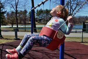 Four-year-old Lyanna Welch of Schenectady seems to be enjoying the feel of the sun on her face as she swings at the playground in Central Park Saturday April 21, 2018 in Schenectady.NY.  (John Carl D'Annibale/Times Union)