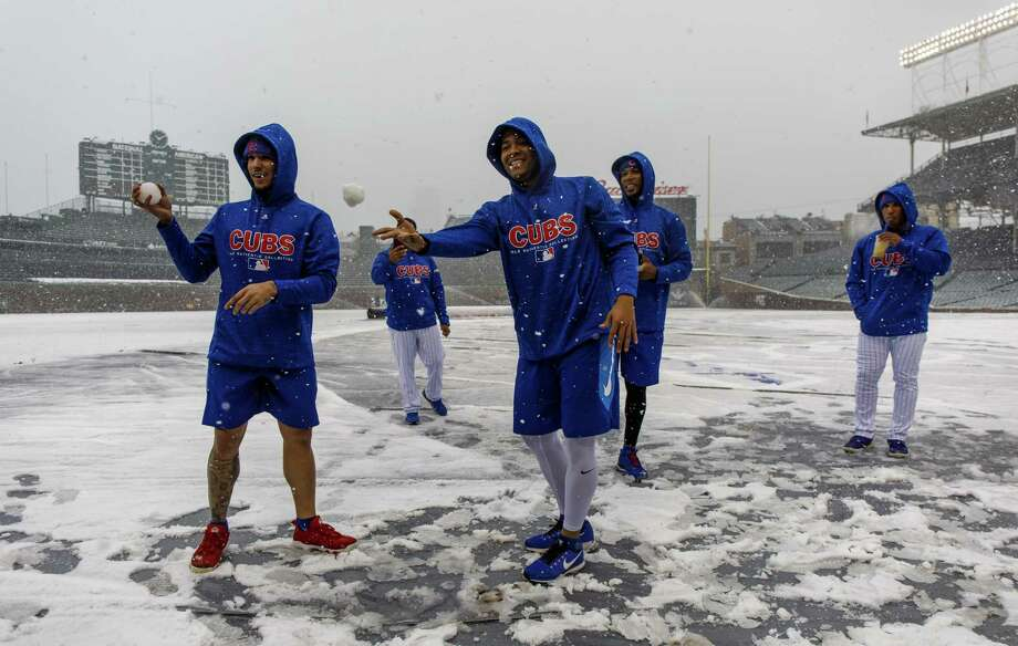 Chicago Cubs players throw snowballs at Wrigley Field in Chicago earlier this month. The Register's Joe Morelli says it's time to at least look at a 150-game MLB slate and start the season in mid-April. Photo: Brian Cassella / Associated Press / Brian Cassella/Chicago Tribune