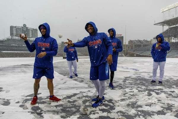 Chicago Cubs players throw snowballs at Wrigley Field in Chicago earlier this month. The Register's Joe Morelli says it's time to at least look at a 150-game MLB slate and start the season in mid-April.