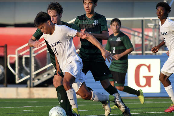Alief Elsik sophomore forward Mayno Linares (11) pushes the ball upfield against a pair of San Antonio Reagan defenders during the first half of their UIL Class 6A State Final Boys Soccer matchup at Birkelbach Field in Georgetown on April 21, 2018. (Photo by Jerry Baker/Freelance)