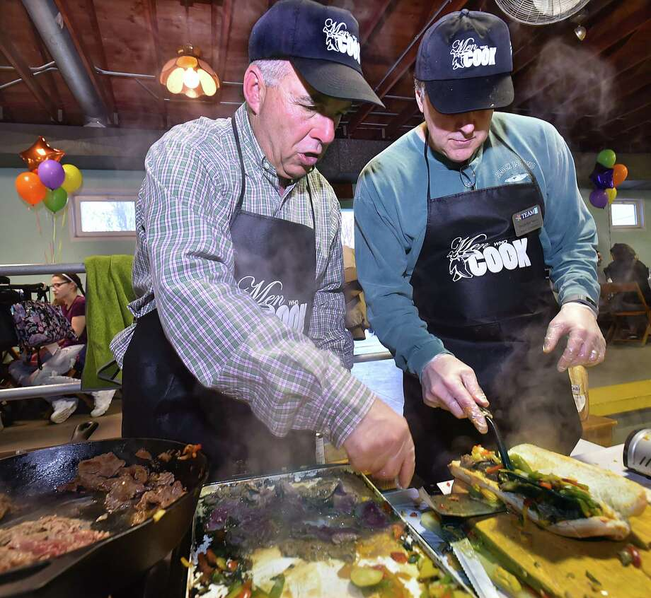 Jeff Merrill, left, and Dave Rabinove make philly cheesesteak sliders at the 11th annual MEN WHO COOK on Saturday, April 21, 2018, at Warsaw Park in Ansonia. The event featured a variety of food prepared by more than 90 men from the area and proceeds will benefit the services offered by TEAM inc. Photo: Catherine Avalone, Hearst Connecticut Media / New Haven Register