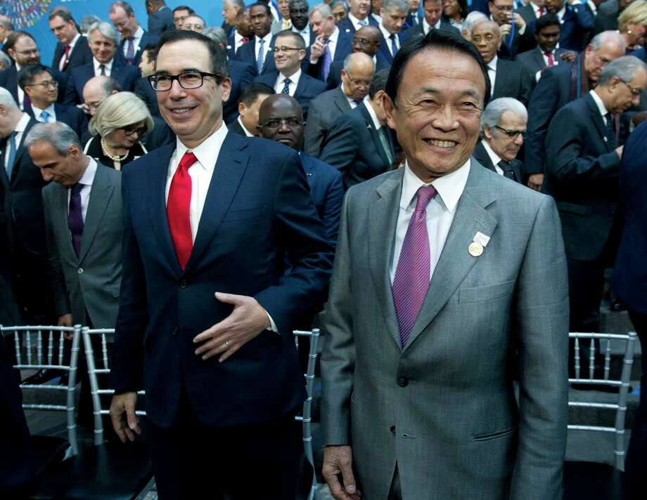U.S. Treasury Secretary Steve Mnuchin, left, and Japan's Finance Minister Taro Aso attend the International Monetary Fund (IMF) Governors group photo at World Bank/IMF Spring Meetings, in Washington, Saturday, April 21, 2018. (AP Photo/Jose Luis Magana) Photo: Jose Luis Magana / FR159526 AP