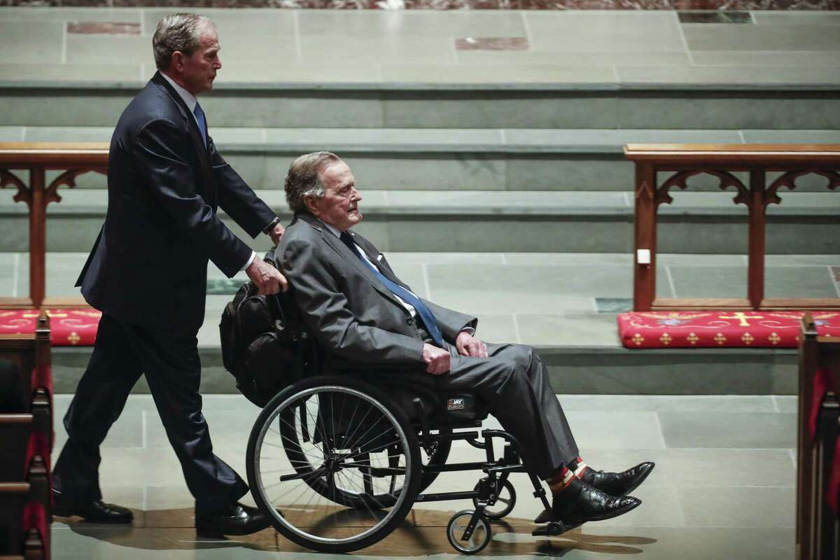 Former president George W. Bush, left, wheels his father, former president George H.W. Bush into the church for the funeral for first lady Barbara Bush at St. Martin's Episcopal Church on Saturday, April 21, 2018, in Houston.