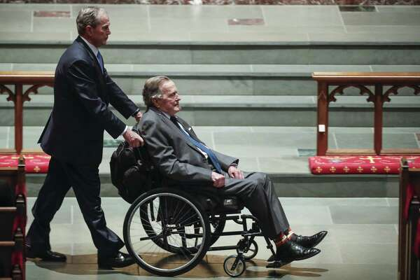 Former president George W. Bush, left, wheels his father, former president George H.W. Bush into the church for the funeral for first lady Barbara Bush at St. Martin's Episcopal Church on Saturday, April 21, 2018, in Houston. ( Brett Coomer / Houston Chronicle, POOL )