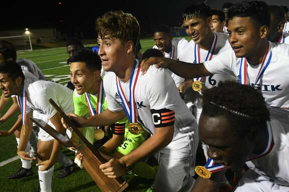 Alief Elsik senior defender Jose Umana (4), center, holds his team's championship trophy as they get ready to show it off to the Elsik fans after their 1-0 win in their UIL Class 6A State Final Boys Soccer matchup at Birkelbach Field in Georgetown on April 21, 2018. (Photo by Jerry Baker/Freelance)