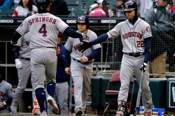 CHICAGO, IL - APRIL 21: George Springer #4 of the Houston Astros is congratulated by Josh Reddick #22 after scoring against the Chicago White Sox on an RBI single by Carlos Correa #1 (not pictured) during the first inning at Guaranteed Rate Field on April 21, 2018 in Chicago, Illinois.  (Photo by Jon Durr/Getty Images)