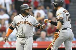 ANAHEIM, CA - APRIL 21:  Third baseman Pablo Sandoval #48 of the San Francisco Giants is congratulated by Evan Longoria #10 after he was driven in on a two-run home run by first baseman Brandon Belt #9 in the second inning at Angel Stadium on April 21, 2018 in Anaheim, California. (Photo by John McCoy/Getty Images)