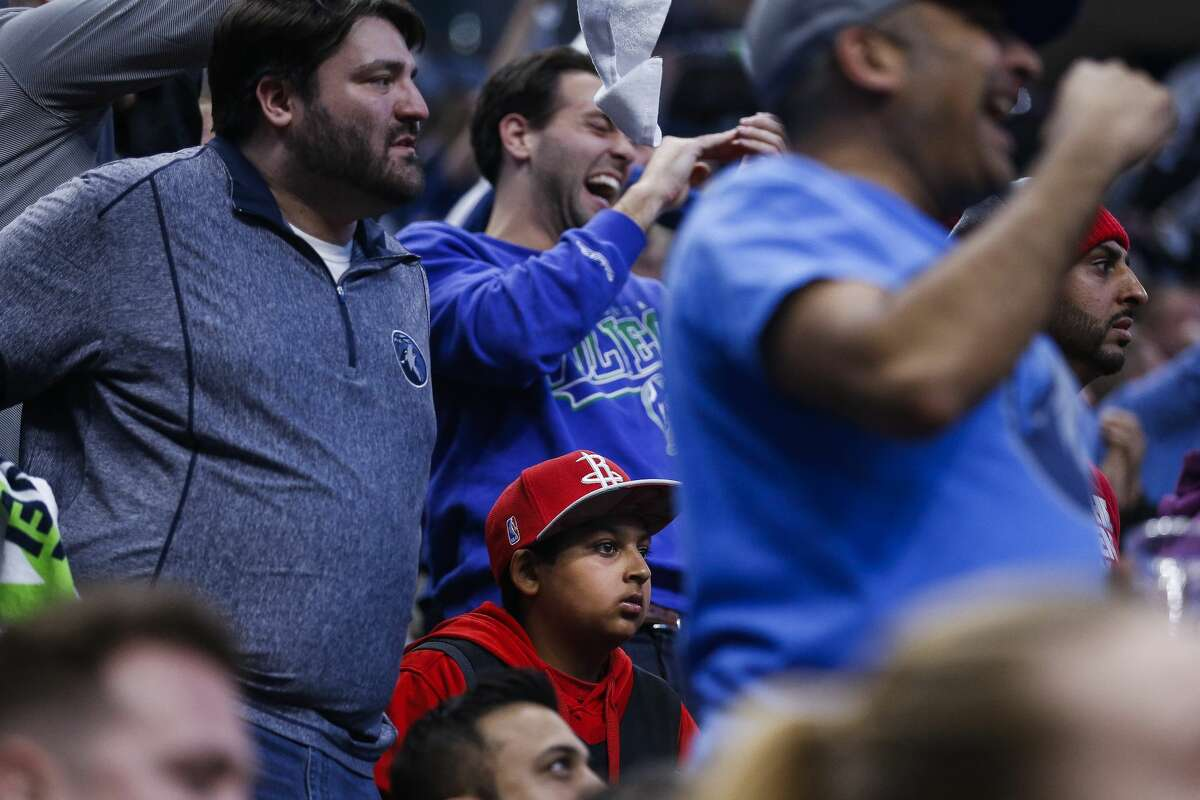 A Houston Rockets fan is surrounded by celebrating Minnesota Timberwolves fans as the Timberwolves pull ahead of the Rockets in Game 3 of the first round of the NBA Playoffs at Target Center Saturday, April 21, 2018 in Minneapolis. (Michael Ciaglo / Houston Chronicle)