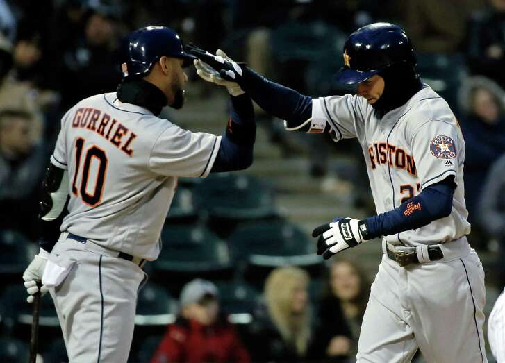 Yuli Gurriel greets Josh Reddick at home plate following Reddick's grand slam in the second inning Saturday night at Chicago. Reddick added a second home run in the fourth inning and finished 2-for-3 with five RBIs.