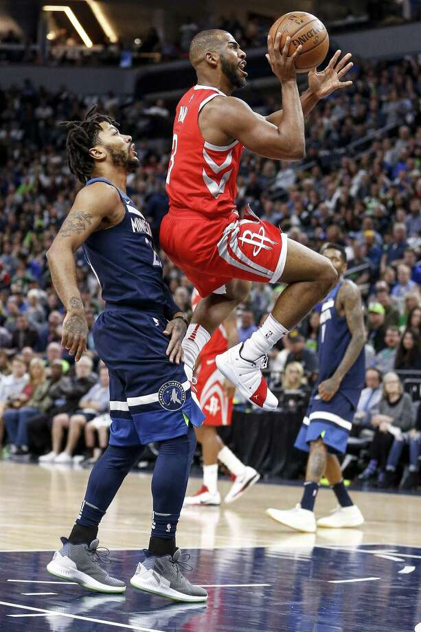 Rockets guard Chris Paul, right, puts up a runner as he passes Timberwolves guard Derrick Rose, left, in Game 3 on Saturday night at Target Center. Photo: Michael Ciaglo, Houston Chronicle / Houston Chronicle / Michael Ciaglo