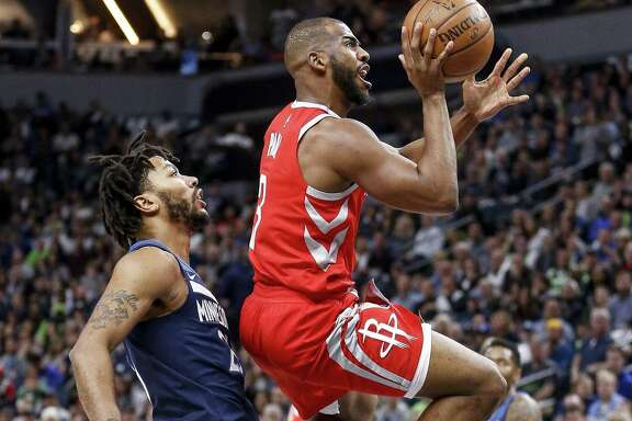 Rockets guard Chris Paul, right, puts up a runner as he passes Timberwolves guard Derrick Rose, left, in Game 3 on Saturday night at Target Center.