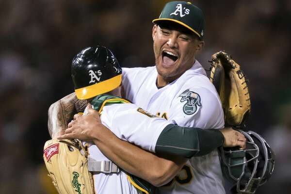 Oakland Athletics starting pitcher Sean Manaea, right, celebrates with catcher Jonathan Lucroy after pitching a no-hitter against the Boston Red Sox during a baseball game in Oakland, Calif., Saturday, April 21, 2018. The A's won 3-0. (AP Photo/John Hefti)