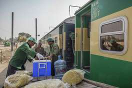 Kitchen staff load food onto a Green Line Express train in Khanewal, Pakistan, on Feb. 20, 2018.