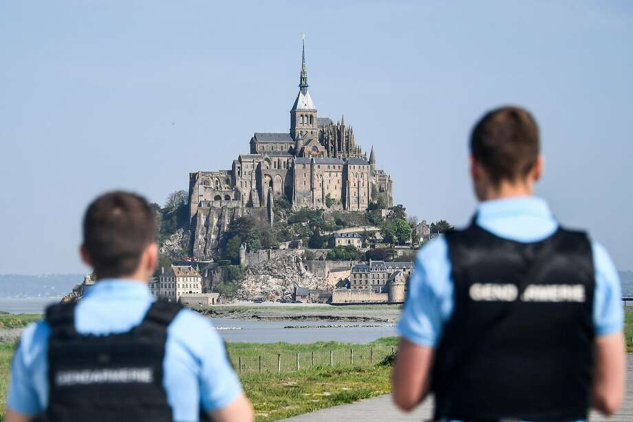 French officers block the road leading to Mont-Saint-Michel after it was evacuated. The order was issued as a precaution after a visitor apparently threatened to attack security services. Photo: Damien Meyer / AFP / Getty Images