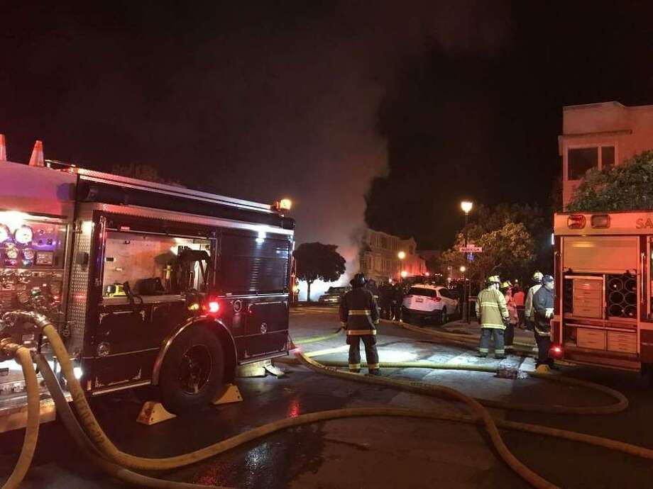 A fire broke out on Eighth Avenue near the corner of Noriega Street on Saturday night. Photo: Sarah Ravani / The Chronicle