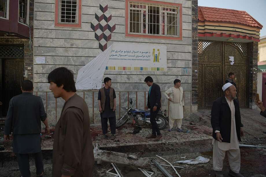 Afghan residents inspect the site of a suicide bombing outside a voter registration centre in Kabul on April 22, 2018. A suicide bomber blew himself up in a crowd outside a voter registration centre in the Afghan capital Kabul on April 22, killing four people and wounding at least 15 in the latest attack on the centres. The assaults underscore growing concerns about security in the lead-up to legislative elections scheduled for October 20.   / AFP PHOTO / SHAH MARAISHAH MARAI/AFP/Getty Images Photo: SHAH MARAI;Shah Marai / AFP / Getty Images
