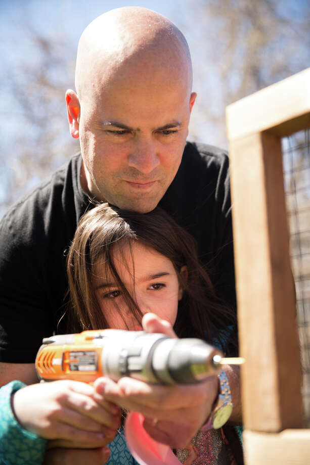 Ian Chodos helps his daughter Sienna drill pilot holes in the new elevated garden at the Temple Sholom Selma Maisel Nursery School in Greenwich, Conn. on Sunday, April 22, 2018. The 8' x 8' raised garden bed will serve as a sensory-rich space to promote student inquiry, dialogue and critical thinking. Photo: Chris Palermo, For Hearst Connecticut Media / Greenwich Time Freelance