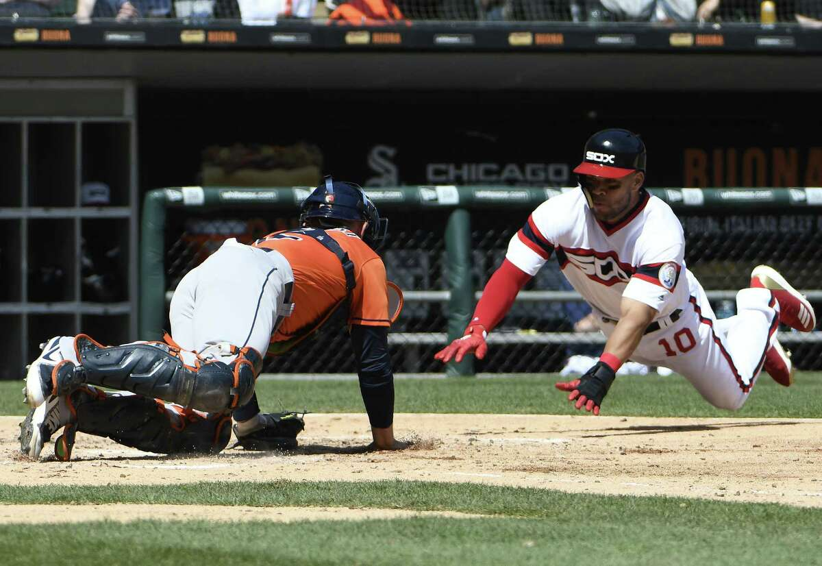 CHICAGO, IL - APRIL 22: Max Stassi #12 of the Houston Astros prepares to tag out Yoan Moncada #10 of the Chicago White Sox at home plate during the third inning on April 22, 2018 at Guaranteed Rate Field in Chicago, Illinois.