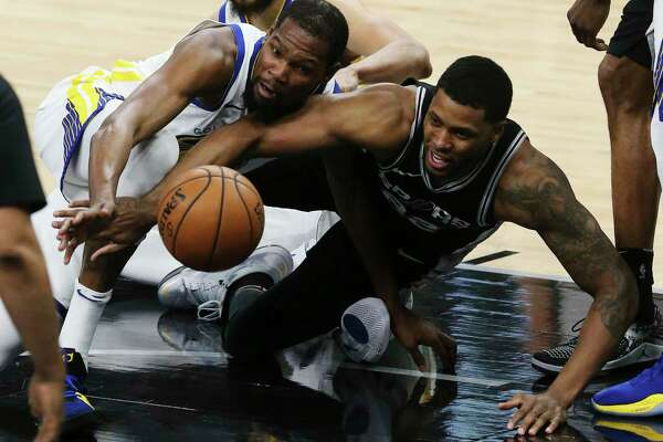 Golden State Warriors' Kevin Durant and San Antonio Spurs' Rudy Gay scramble for a loose ball during the first half at the AT&T Center, Sunday, April 22, 2018.