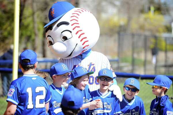 Players from the Research Park Deli team excitedly pose for a photo with Mr. Met following the Opening Day Little League Ceremony held on Caporizzo Field in Stamford, Conn. on Sunday, April 22, 2018.