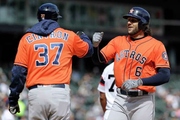 Houston Astros' Jake Marisnick, right, celebrates with first base coach Alex Cintron after hitting a single against the Chicago White Sox during the seventh inning of a baseball game Sunday, April 22, 2018, in Chicago. (AP Photo/Nam Y. Huh)