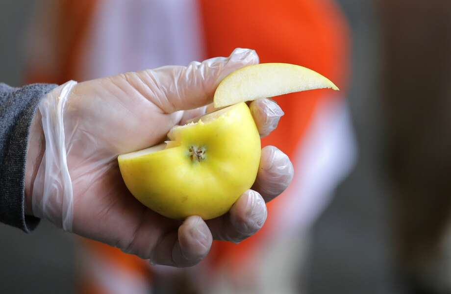 FILE – In this photo taken Wednesday, April 4, 2018, a vendor hands-off sliced samples of a Washington state-grown opal apple to customers at the the Pike Place Market in Seattle. (AP Photo/Elaine Thompson) Photo: Elaine Thompson/AP