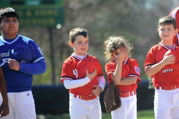Eight-year-old Cyrus Muslim, center right, covers his face with his hand during Opening Day Little League Ceremony held on Caporizzo Field in Stamford, Conn. on Sunday, April 22, 2018. Also pictured is nine-year-old teammate Evan DeMarco.