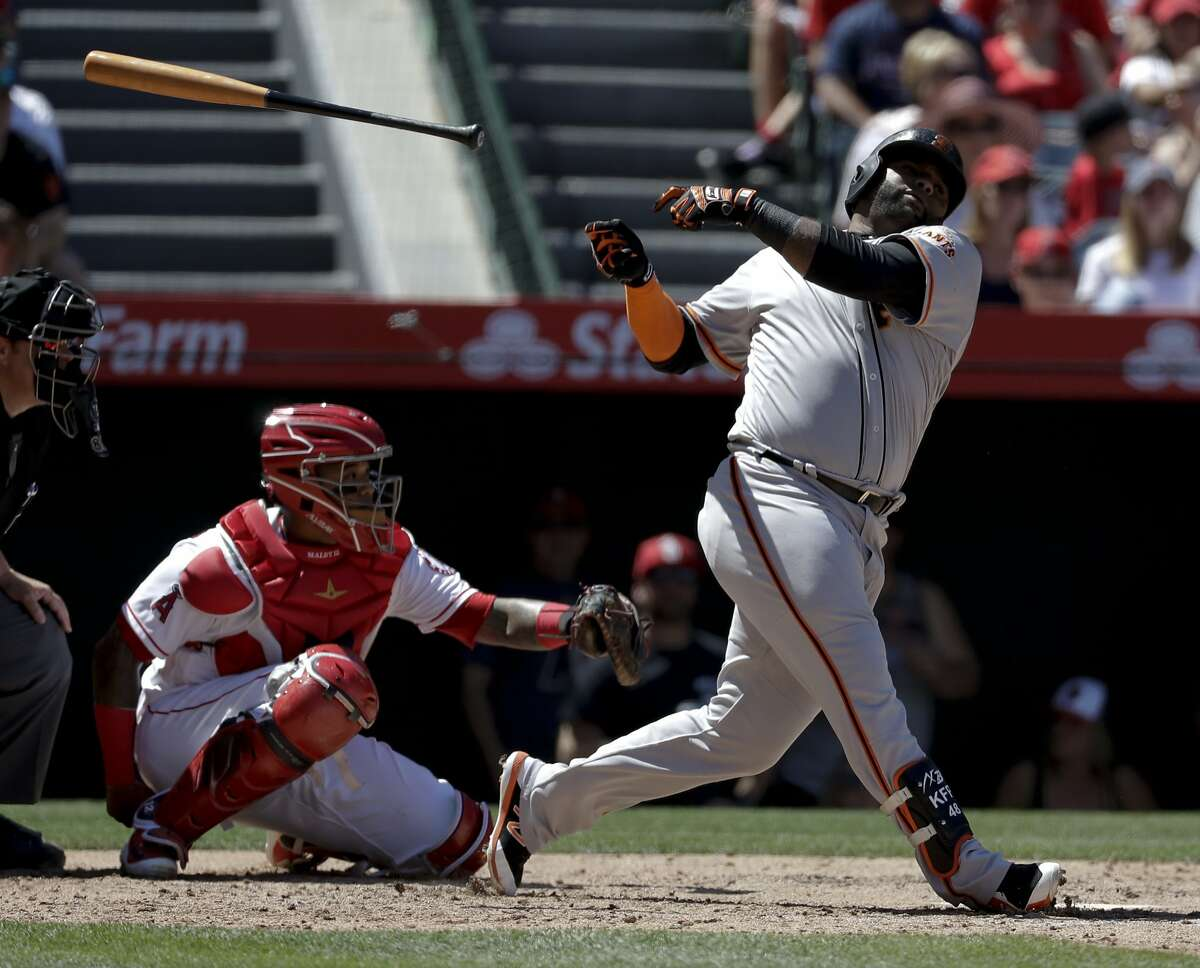 San Francisco Giants' Pablo Sandoval, right, lets go of his bat during the third inning of a baseball game against the Los Angeles Angels in Anaheim, Calif., Sunday, April 22, 2018.