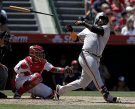 San Francisco Giants' Pablo Sandoval, right, lets go of his bat during the third inning of a baseball game against the Los Angeles Angels in Anaheim, Calif., Sunday, April 22, 2018. (AP Photo/Chris Carlson)