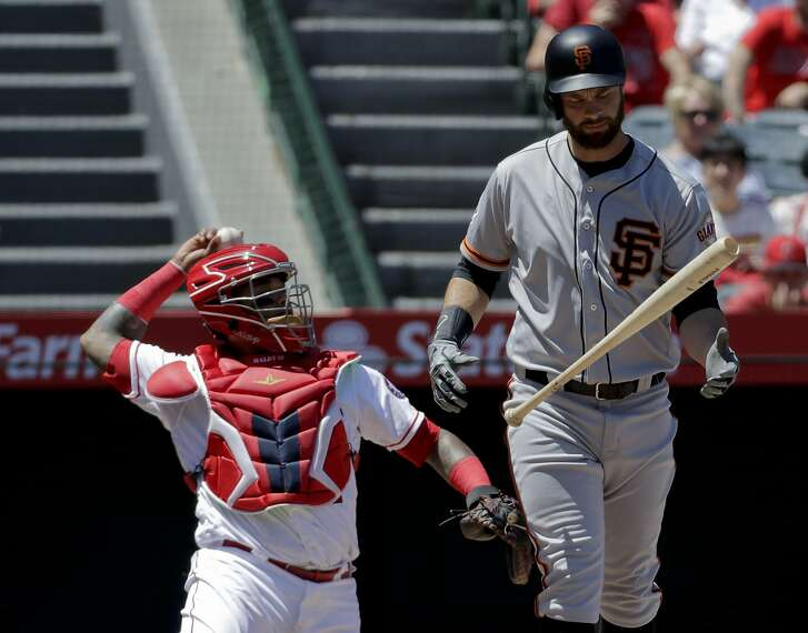 San Francisco Giants' Brandon Belt, right, reacts after hitting a foul ball during the first inning of a baseball game against the Los Angeles Angels in Anaheim, Calif., Sunday, April 22, 2018. (AP Photo/Chris Carlson)