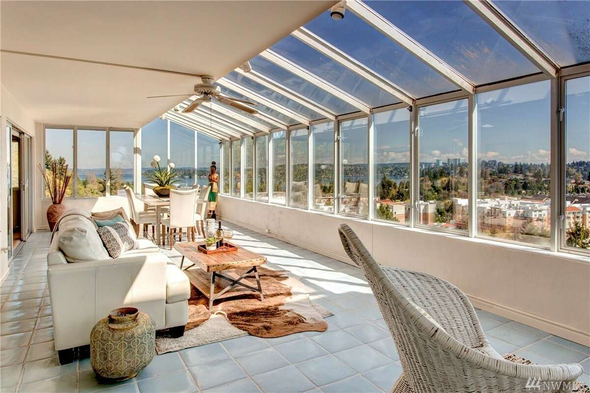Mid-century modern penthouse condo with huge glass solarium offers stunning Mercer Island views.