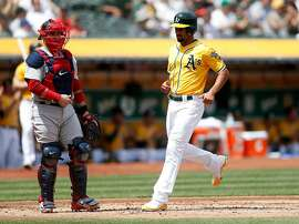 Oakland Athletics' Marcus Semien (10) scores a run off a single hit by Oakland Athletics' Khris Davis (2) against the Boston Red Sox in the first inning on Sunday, April 22, 2018 at the Oakland Coliseum in Oakland, Calif. (Nhat V. Meyer/Bay Area News Group/TNS)